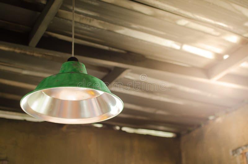 Las lámparas viejas verdes cuelgan arriba en techo de una casa abandonada foto de archivo
