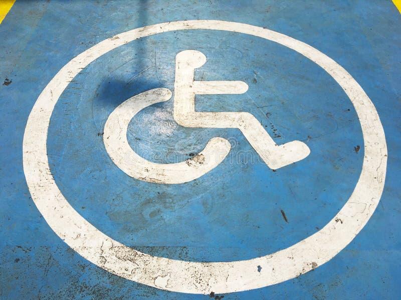 Las líneas blancas muestra de estacionamiento discapacitado en azul pintaron el st concreto fotografía de archivo