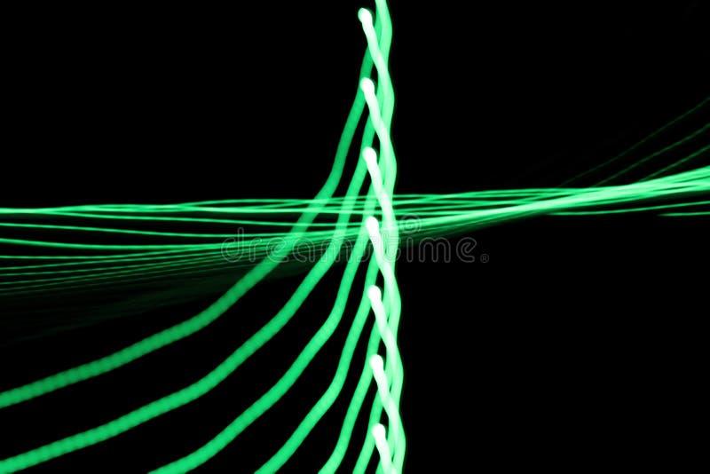 Las líneas ligeras de neón y las curvas verdes resumen imagen en fondo negro imagen de archivo
