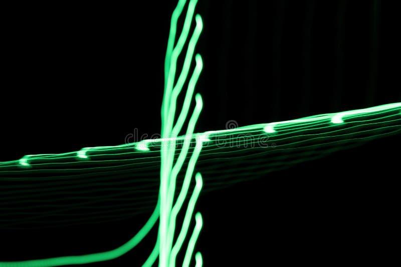 Las líneas ligeras de neón y las curvas verdes resumen imagen en fondo negro foto de archivo libre de regalías