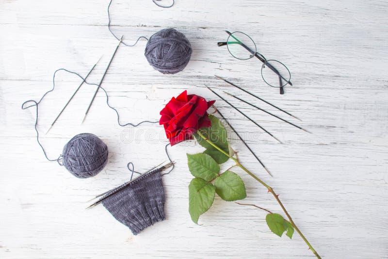 Las lanas que hacían punto grises, la mitad del calcetín hecho a mano en agujas, los vidrios negros y el solo rojo subieron en fo fotografía de archivo