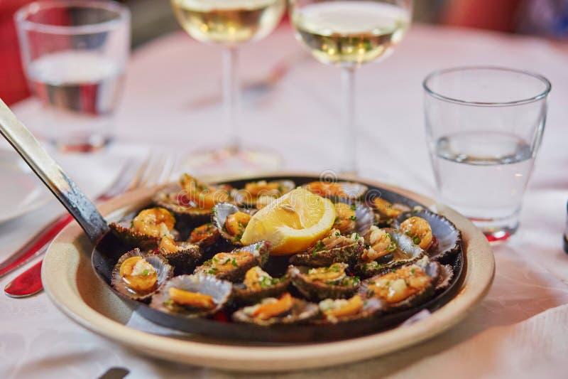 Las lapas asadas a la parrilla sirvieron con el limón - mariscos tradicionales en la isla de Madeira, Portugal imagenes de archivo