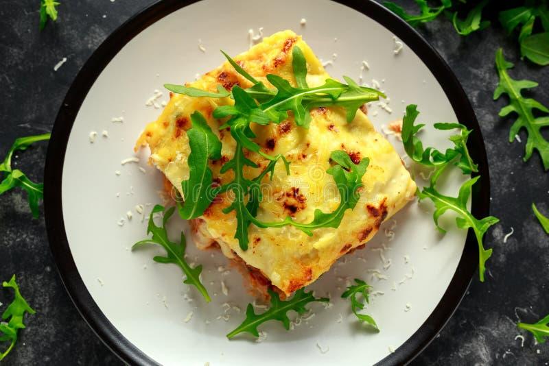 Las lasañas hechas en casa con la carne de vaca picadita boloñés y el bechamel sauce remataron el arugula salvaje, queso parmesan imagen de archivo