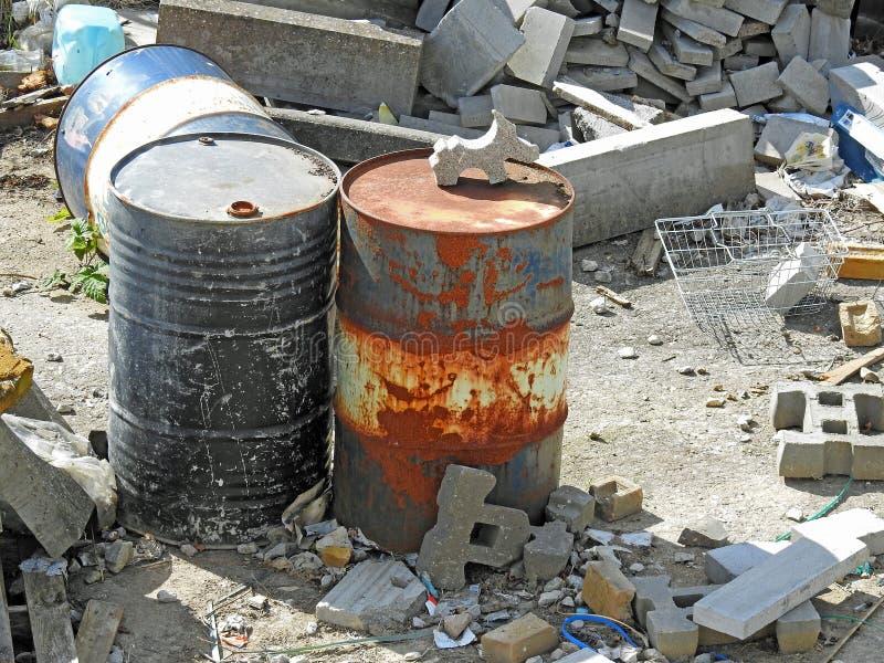 Las latas del aceite del sitio de los desperdicios de la basura del daño del daño medioambiental inclinan el edificio foto de archivo