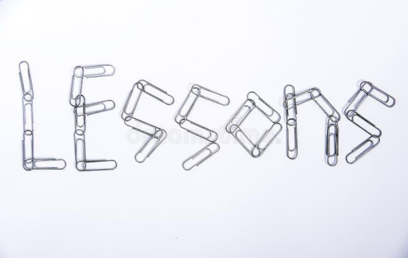 Las lecciones son una palabra hecha de los clips de papel del metal imágenes de archivo libres de regalías