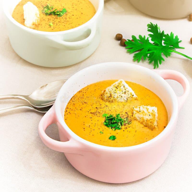 Las lentejas rojas baten la sopa con los bizcochos tostados en pequeños potes o cuenco de la porción fotos de archivo libres de regalías