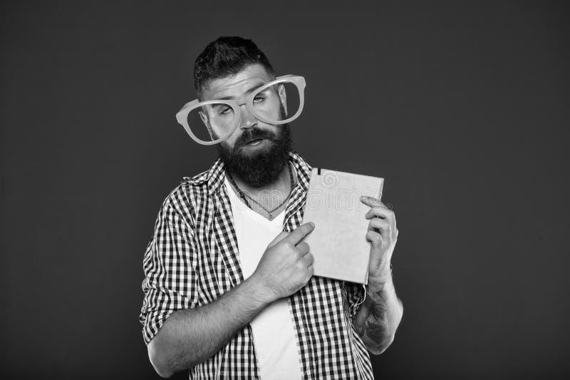 Las lentes divertidas del hombre barbudo del inconformista sostienen la libreta o el libro Lea este libro Sentido c?mico y del hu fotografía de archivo libre de regalías