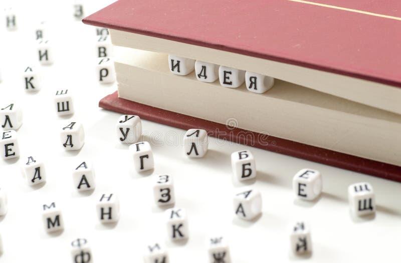 Las letras cirílicas escritas idea del triunfo de la palabra entre las hojas del libro y las letras cirílicas dispersan en el ext foto de archivo