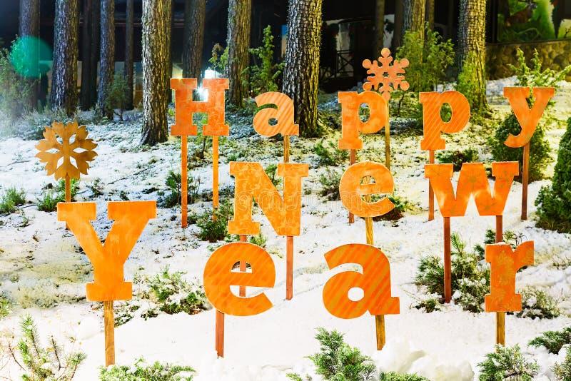 Las letras de la Feliz Año Nuevo se cierran para arriba en pueblo del bosque del invierno foto de archivo libre de regalías