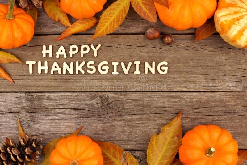 Las letras de madera de la acción de gracias feliz con otoño doblan la frontera en la madera foto de archivo libre de regalías