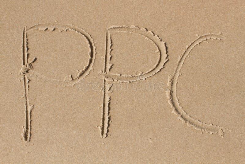 Las letras P P C dibujadas en la arena foto de archivo