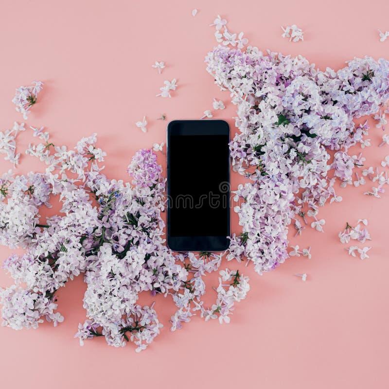 Las lilas elegantes del ramo del teléfono de la endecha plana pican la opinión superior del fondo foto de archivo