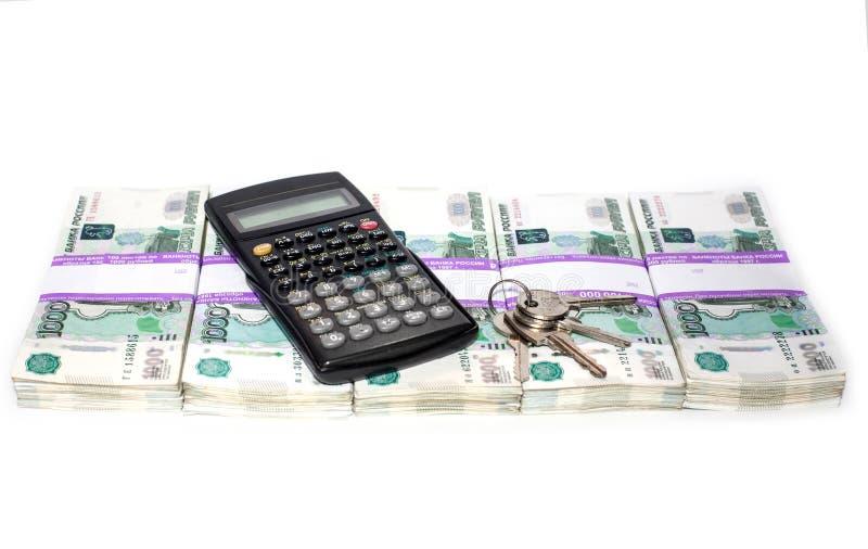 Las llaves de la calculadora y del apartamento en paquetes de dinero presentaron en fila los bancos y concepto de la hipoteca foto de archivo