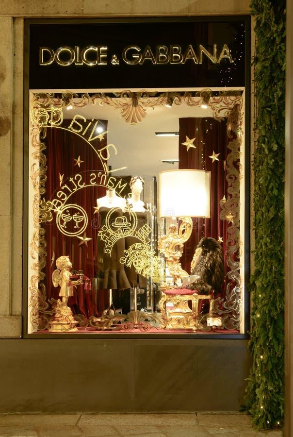 Las luces de la Navidad reflejan en el escaparate de la moda, Milán, Italia imagenes de archivo