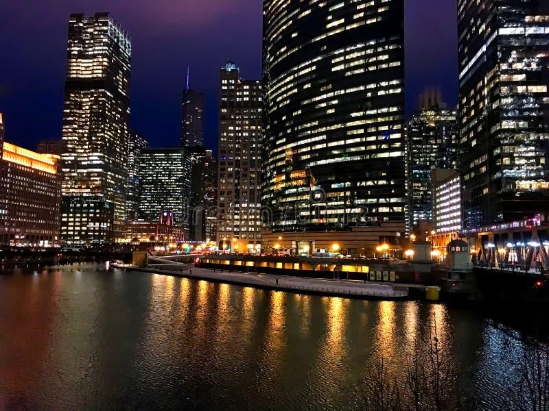 Las luces de la noche de la ciudad reflejan sobre un río Chicago casi congelado en el lazo durante hora punta de la tarde del inv fotos de archivo