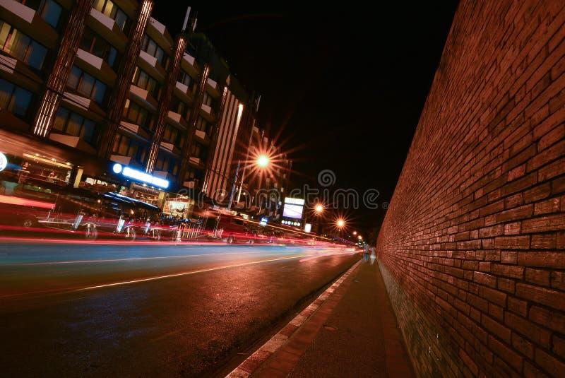 Las luces de los coches en Tha Pae Gate en la noche con muchos Tuk Tuk parquearon junto al camino, en Chiang Mai fotos de archivo