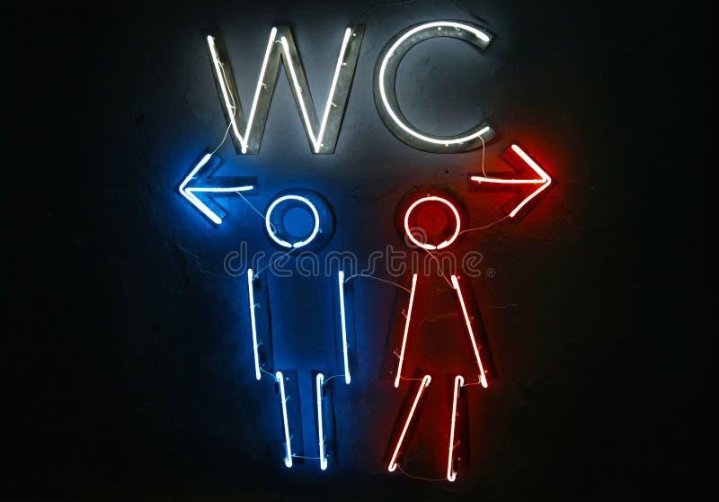 Las luces de neón del retrete del WC firman con direcciones imagenes de archivo