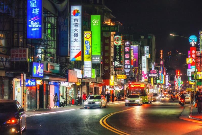 Las luces de neón de la vida nocturna de Taipei llevan en taxi las calles apretadas de la ciudad foto de archivo