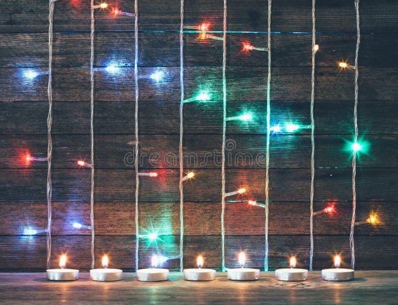 Las luces, las guirnaldas y las velas coloreadas en el fondo del granero viejo suben imágenes de archivo libres de regalías