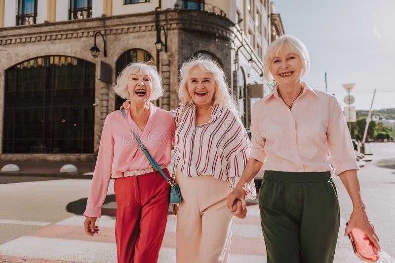 Las más viejas señoras de risa están llevando a cabo las manos al aire libre imagen de archivo libre de regalías