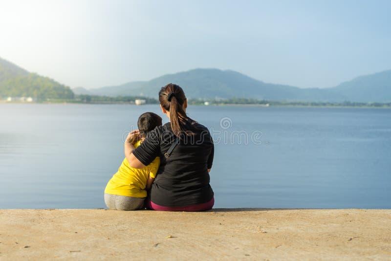 Las madres y los niños se sientan en el depósito de Phra de la explosión en los soles imagen de archivo