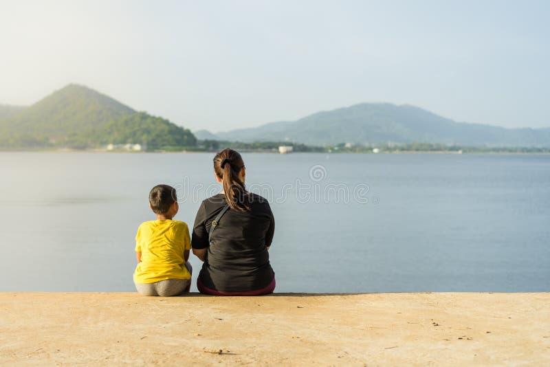 Las madres y los niños se sientan en el depósito de Phra de la explosión en los soles fotografía de archivo