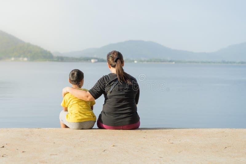 Las madres y los niños se sientan en el depósito de Phra de la explosión en los soles imagenes de archivo