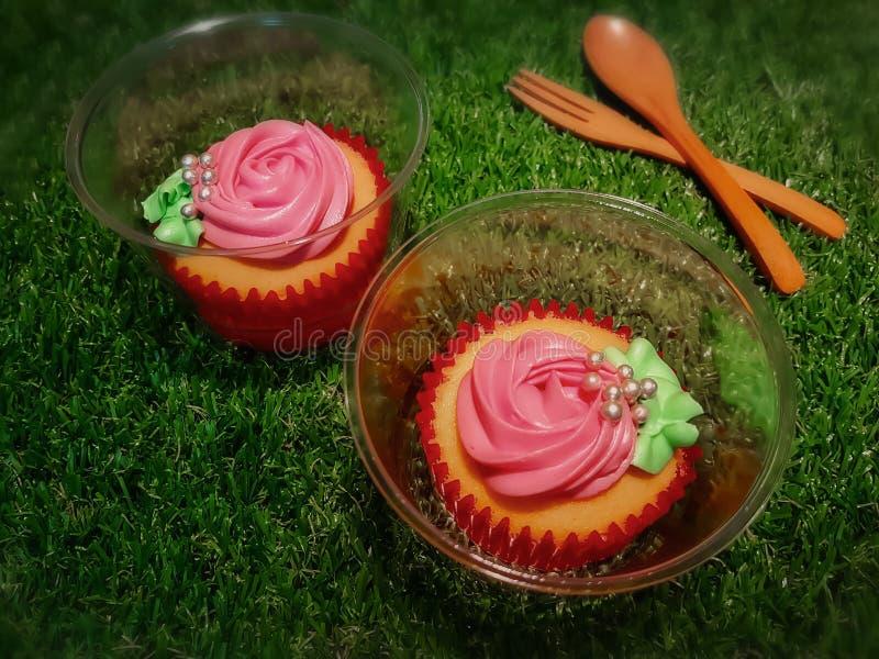 Las magdalenas de la vainilla en tazas de papel rojas y tazas del pl?stico transparente adornaron con las rosas rosadas cremosas  imagen de archivo libre de regalías