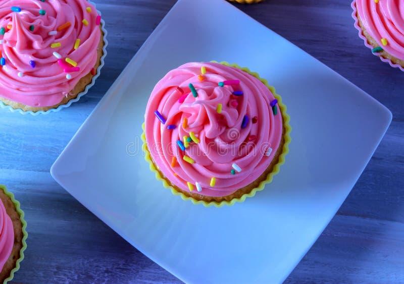 Las magdalenas del cumpleaños, el helar rosado con el arco iris asperjan en una placa blanca imágenes de archivo libres de regalías