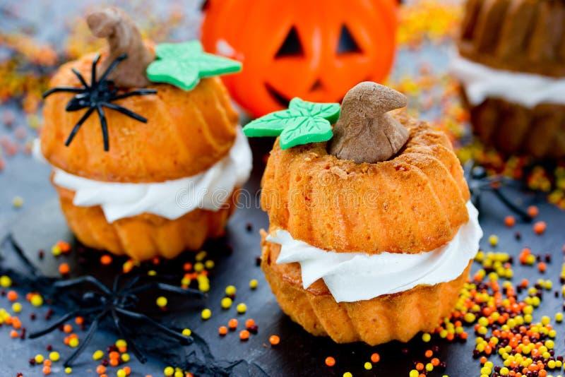 Las magdalenas divertidas de Halloween formaron la calabaza con la crema, creativa y fotografía de archivo libre de regalías