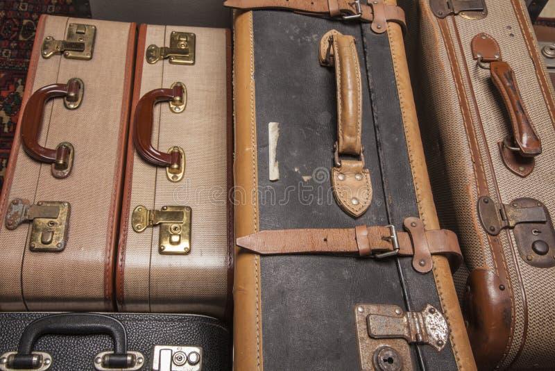 Las maletas antiguas, retro, yacen sobre la mesa con fondo blanco imagen de archivo