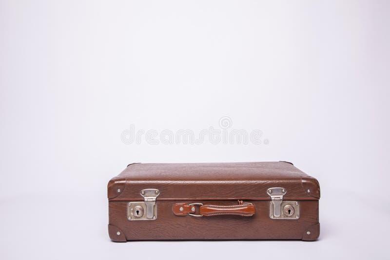 Las maletas antiguas, retro, yacen sobre la mesa con fondo blanco imagen de archivo libre de regalías