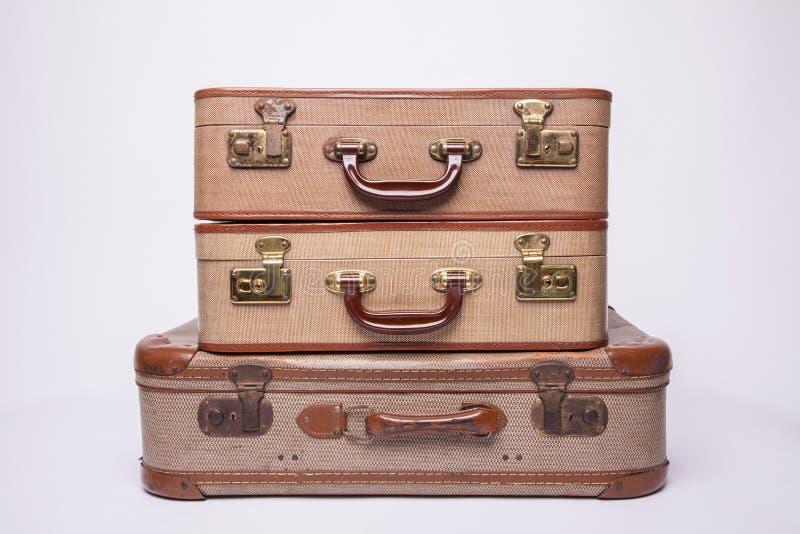 Las maletas antiguas, retro, yacen sobre la mesa con fondo blanco fotografía de archivo