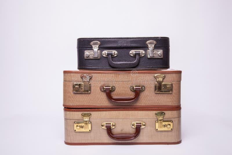 Las maletas antiguas, retro, yacen sobre la mesa con fondo blanco fotos de archivo
