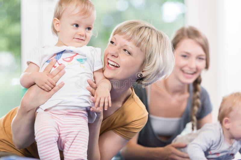 Las mamáes jovenes y sus pequeños niños en madre y niño cursan fotografía de archivo