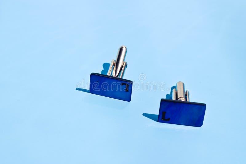 Las mancuernas de los hombres azules profundos del fashin en fondo azul claro imagen de archivo