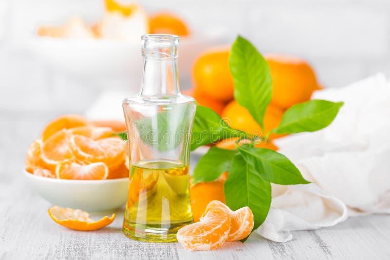 Las mandarinas con las hojas y la botella de fruta cítrica esencial engrasan en un fondo blanco imagenes de archivo
