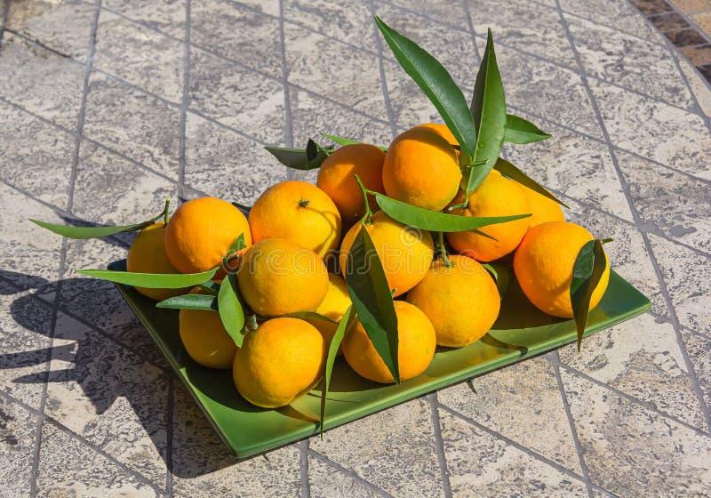 Las mandarinas frescas están sobre la mesa de mosaico de piedra en placa verde imágenes de archivo libres de regalías