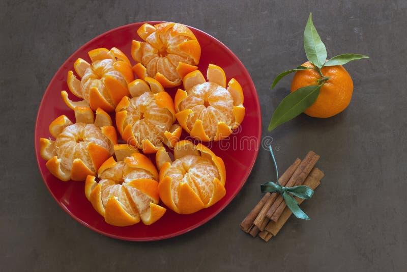 Las mandarinas jugosas brillantes mienten en una placa roja Palillos de canela atados foto de archivo