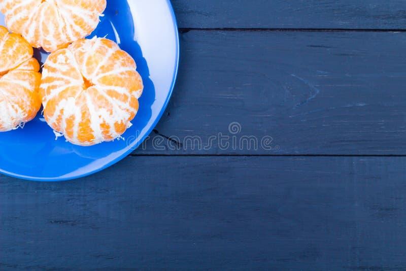 Las mandarinas peladas en una placa azul foto de archivo libre de regalías