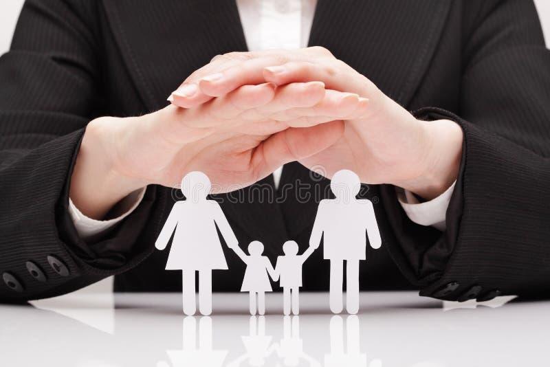 Las manos abrazan a la familia (el concepto) foto de archivo