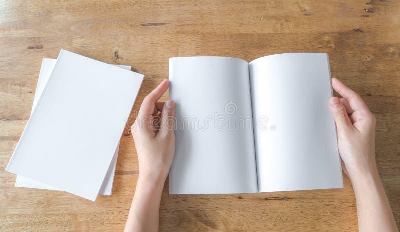 Las manos abren el catálogo en blanco, revistas, mofa del libro para arriba en la madera foto de archivo