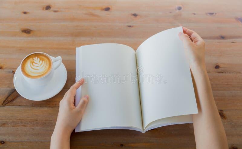 Las manos abren el catálogo en blanco, revistas, mofa del libro para arriba en la tabla de madera imagen de archivo libre de regalías