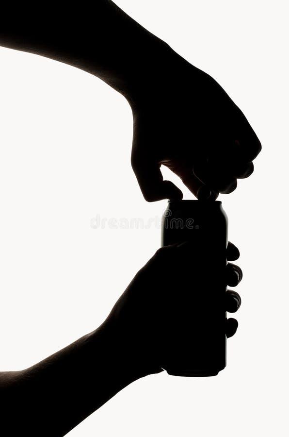 Las manos abren una lata con una bebida imagen de archivo