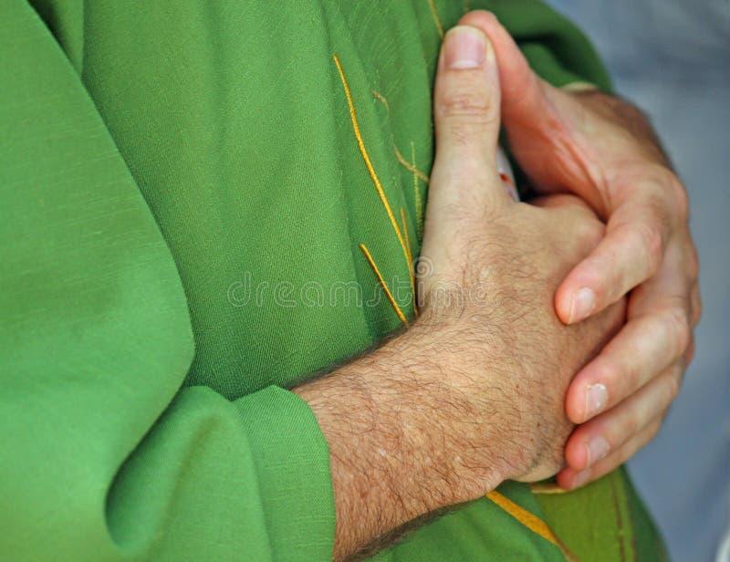 Las manos abrocharon en rezo al sacerdote con la alineada fotos de archivo libres de regalías