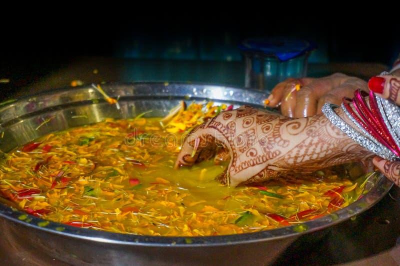 Las manos adornadas de la novia india en agua de la cúrcuma foto de archivo libre de regalías