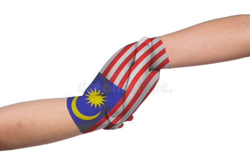 Las manos amigas de dos niños con Malasia señalan por medio de una bandera pintado fotografía de archivo