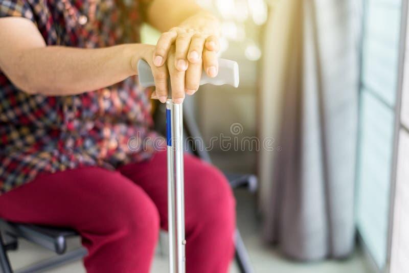 Las manos asiáticas mayores que sostienen el bastón o el palillo que camina, se cierran para arriba foto de archivo libre de regalías