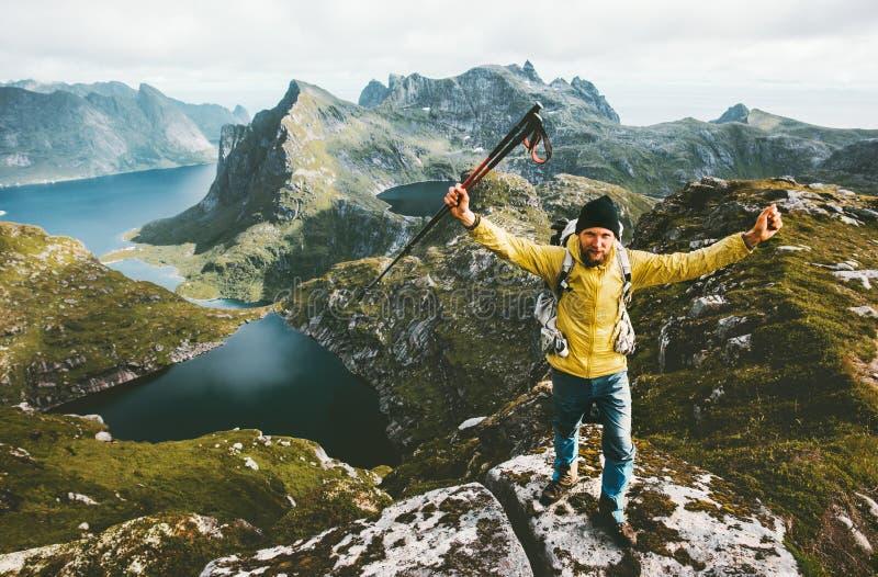 Las manos aumentadas éxito feliz del hombre del viajero que se colocan en la montaña rematan imagen de archivo