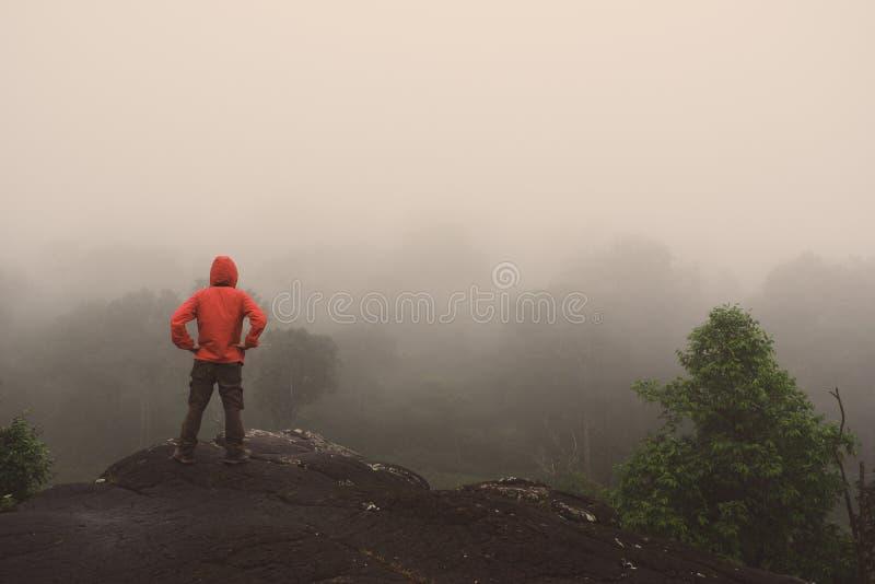 Las manos aumentadas hombre del viajero que se colocan en las montañas del acantilado se aventuran vacaciones de verano del conce imagen de archivo